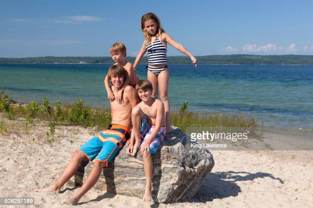 Caucasian cousins standing on rock at beach
