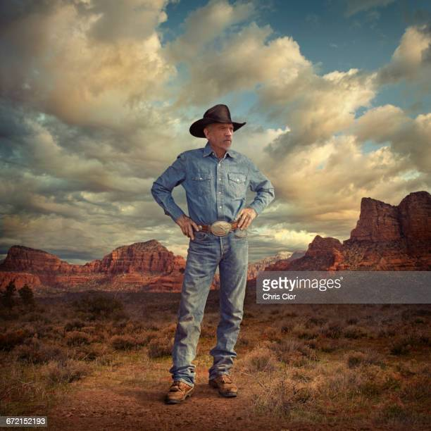 Caucasian cowboy standing with hands on hips in desert landscape