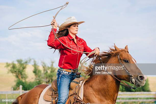 caucasian cowgirl throwing lasso on horseback - lasso stockfoto's en -beelden