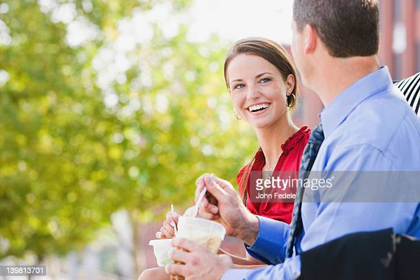 caucasian co-workers having lunch together outdoors - lunch break stock photos and pictures