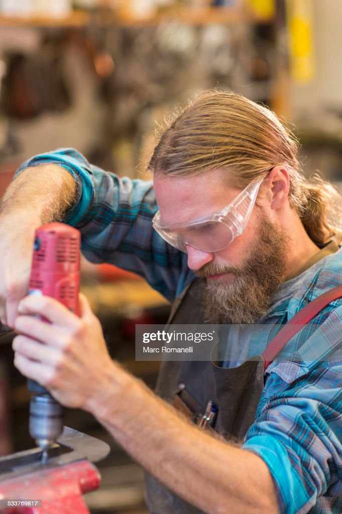 Caucasian craftsman drilling in workshop : Foto stock