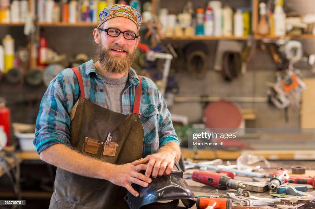 Caucasian craftsman smiling in workshop : Foto stock