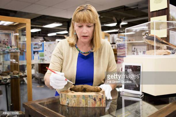 caucasian curator examining artifact in museum - museum curator stock pictures, royalty-free photos & images