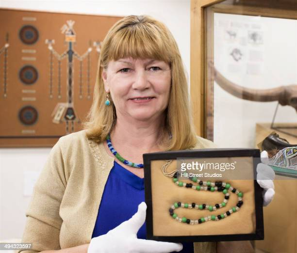 Caucasian curator holding ancient beads in museum