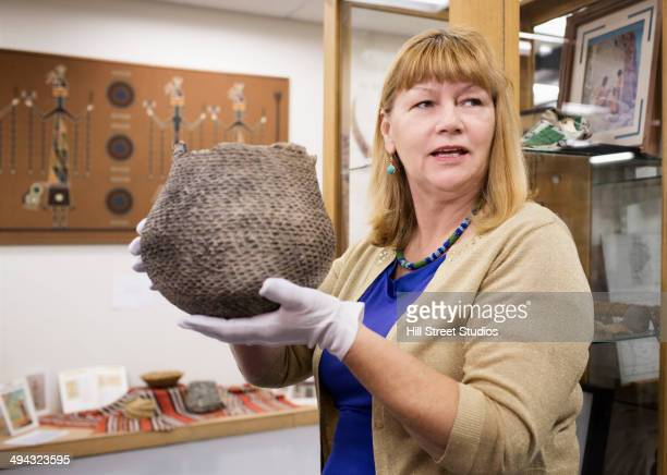 caucasian curator holding artifact in museum - museum curator stock pictures, royalty-free photos & images