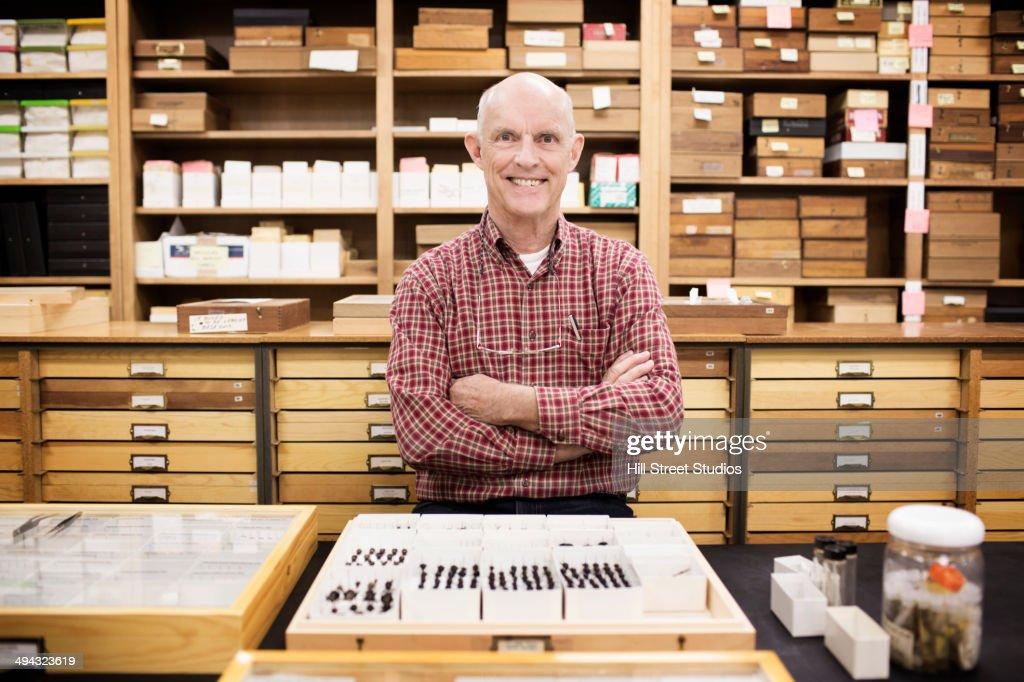 Caucasian curator with bug specimens in museum : Stock Photo