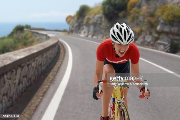 caucasian cyclist cheering on remote coastal road - sportlerin stock-fotos und bilder