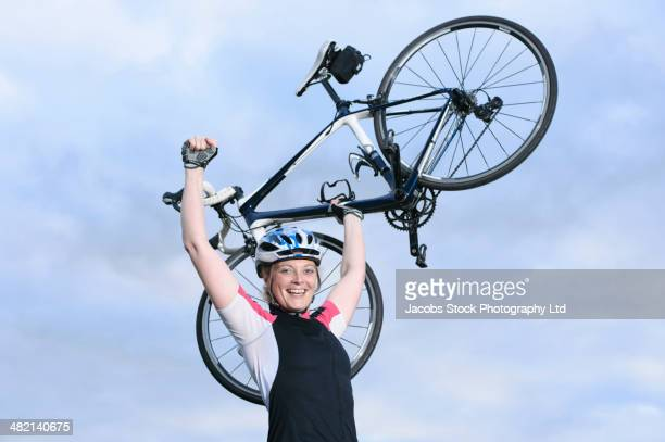Caucasian cyclist holding bicycle overhead