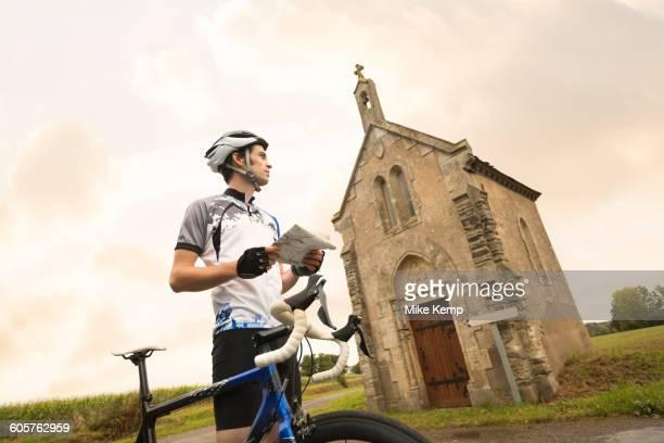 Caucasian cyclist reading map near church
