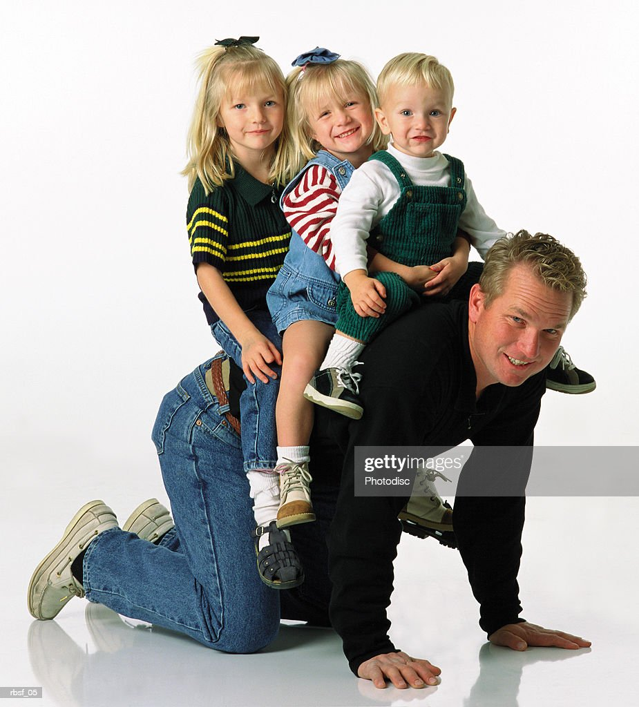 caucasian dad giving three small blonde children a ride on his back : Stock Photo