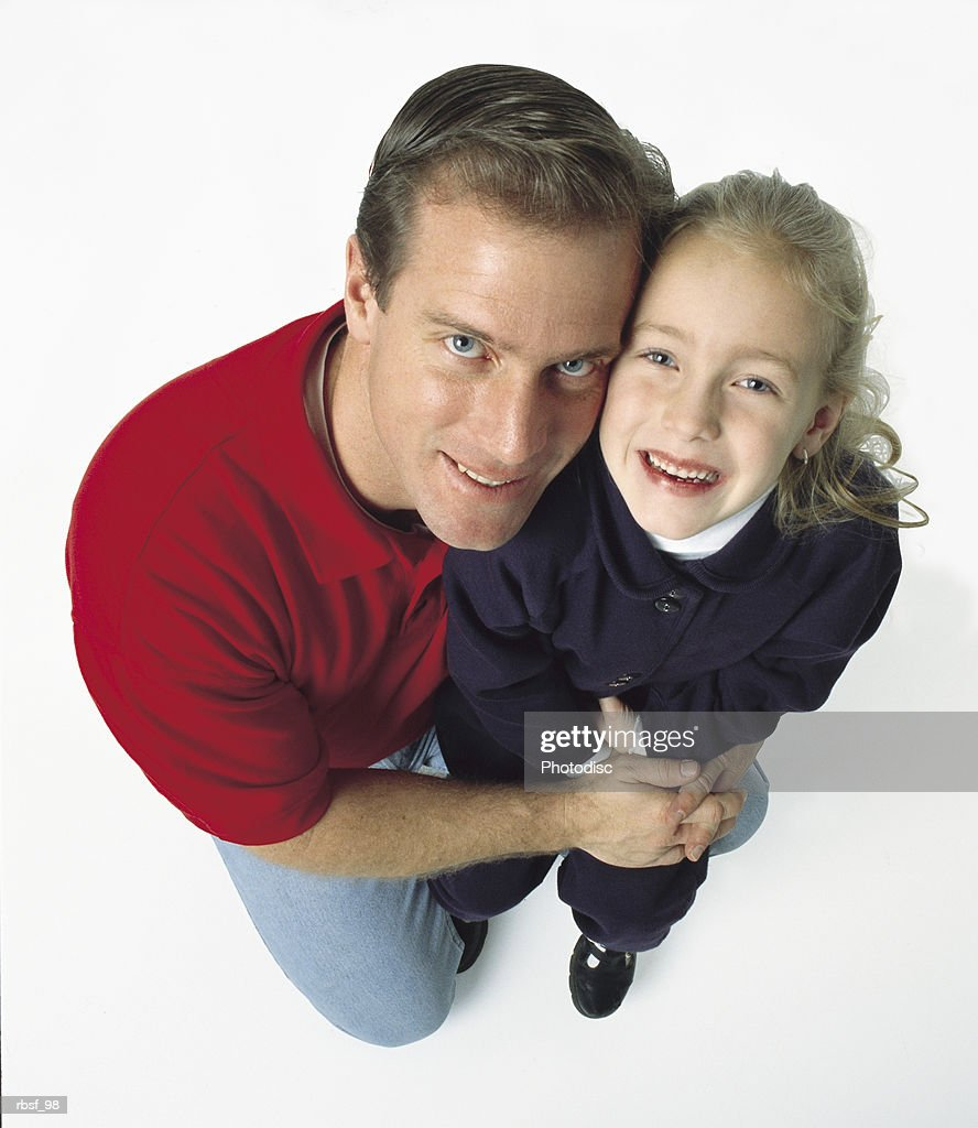 caucasian dad on one knee holds his blonde daughter while both smile big : Stockfoto