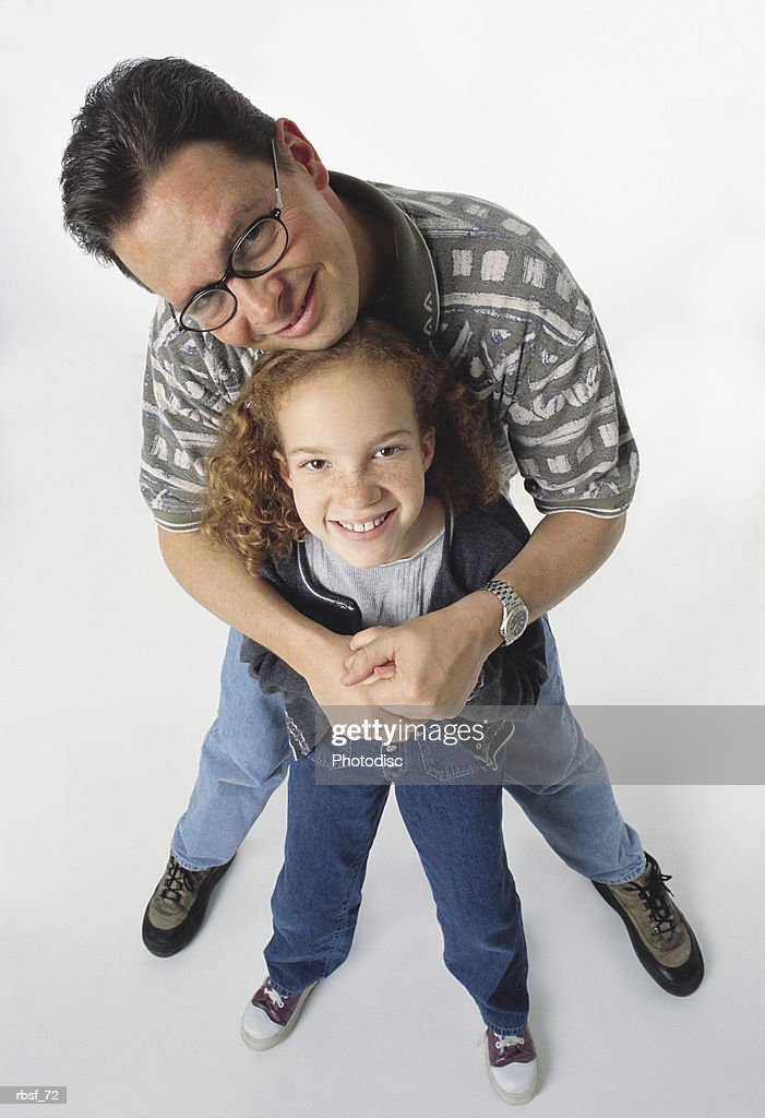 caucasian dad stands behind and holds young redhead daughter who smiles looking up : Foto de stock