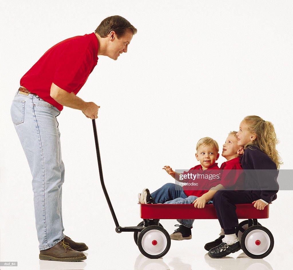 caucasian dad talks to three kids in a red wagon : Foto de stock