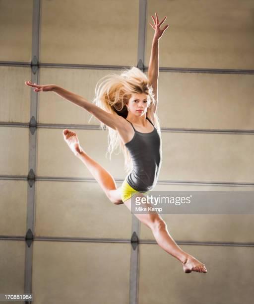 Caucasian dancer leaping in studio