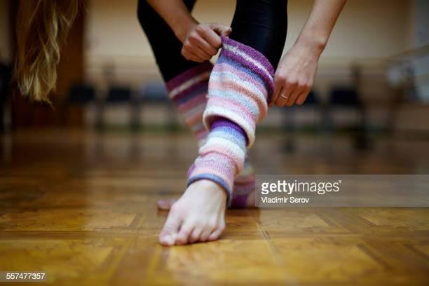 caucasian dancer pulling on leg warmers - レッグウォーマー ストックフォトと画像