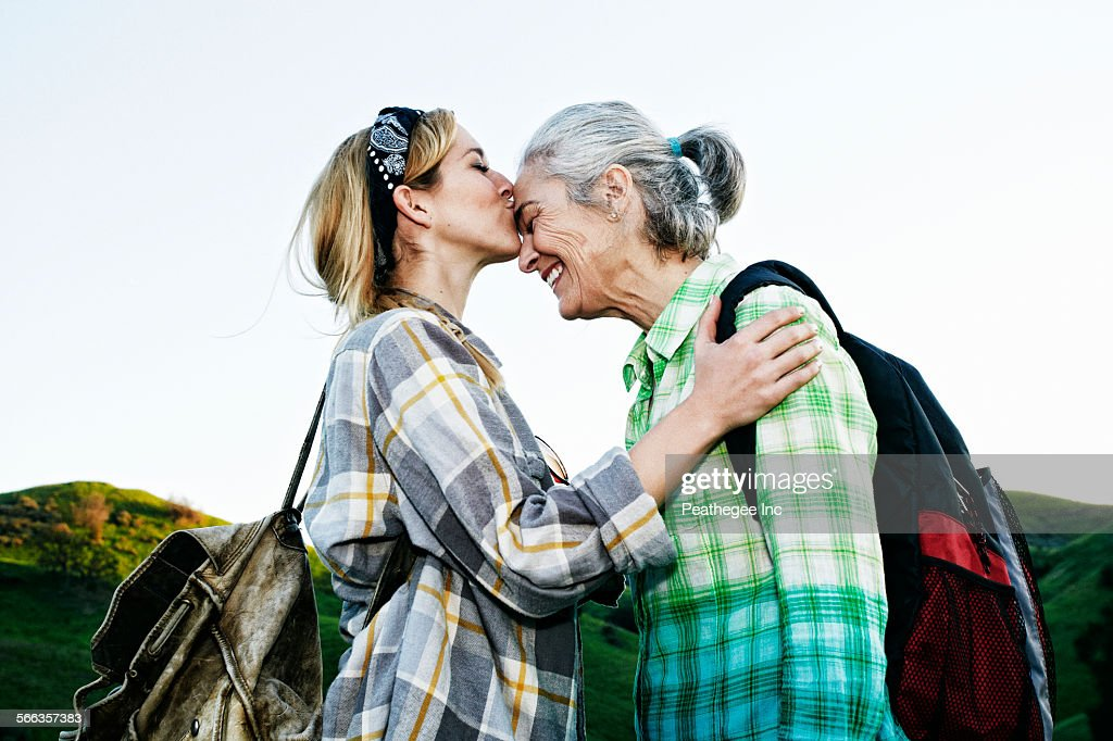 Caucasian daughter kissing mother on rural hilltop : Stock Photo