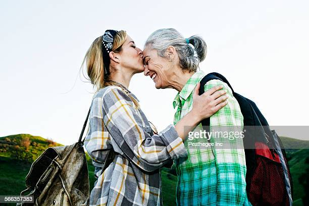 caucasian daughter kissing mother on rural hilltop - adults only stock pictures, royalty-free photos & images