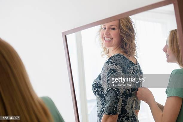 Caucasian daughter zipping dress for mother
