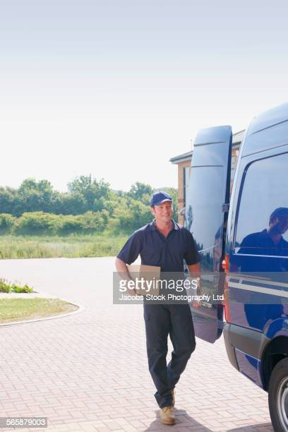Caucasian delivery man carrying package