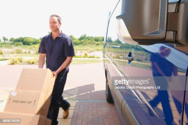 caucasian delivery man wheeling packages - spalding england stock photos and pictures