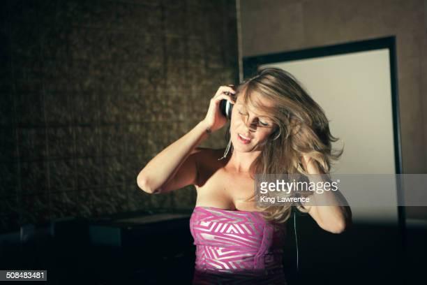 Caucasian disc jockey listening to headphones at nightclub