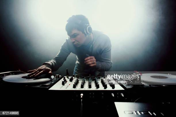 Caucasian disc jockey playing music in nightclub