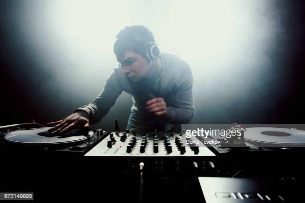 caucasian disc jockey playing music in nightclub - クラブdj ストックフォトと画像