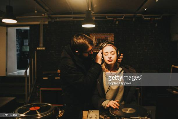 caucasian dj holding headphones on woman - hi fi stock pictures, royalty-free photos & images