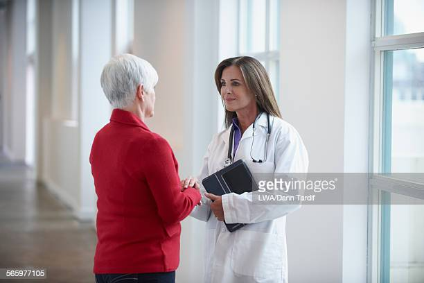 Caucasian doctor and patient talking in hallway
