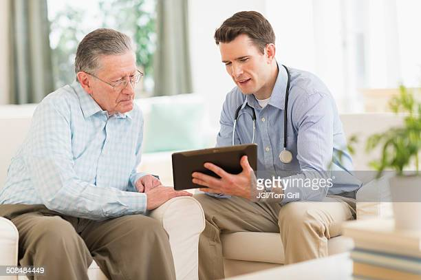 caucasian doctor and patient using digital tablet at home - visita imagens e fotografias de stock
