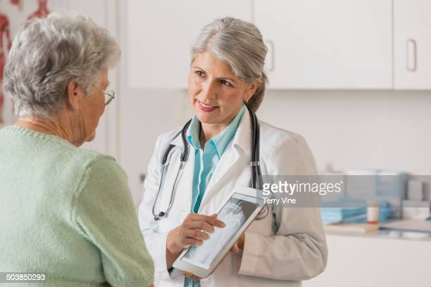 Caucasian doctor and patient using digital tablet in office
