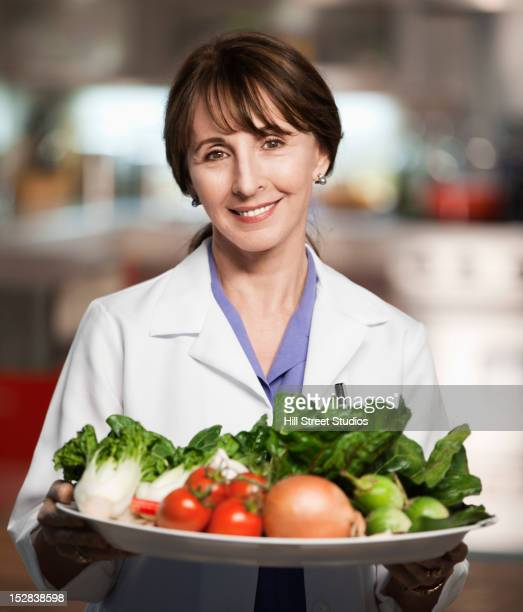 Caucasian doctor holding platter of vegetables