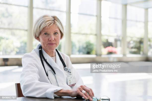 caucasian doctor sitting in empty office - jetta productions stock pictures, royalty-free photos & images