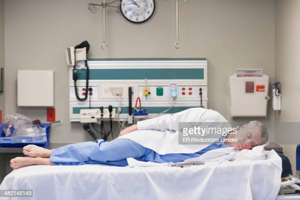 Caucasian doctor sleeping on hospital bed