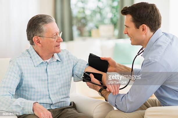 Caucasian doctor taking patient's blood pressure at home
