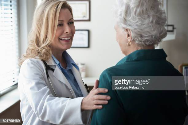 Caucasian doctor talking to patient in clinic