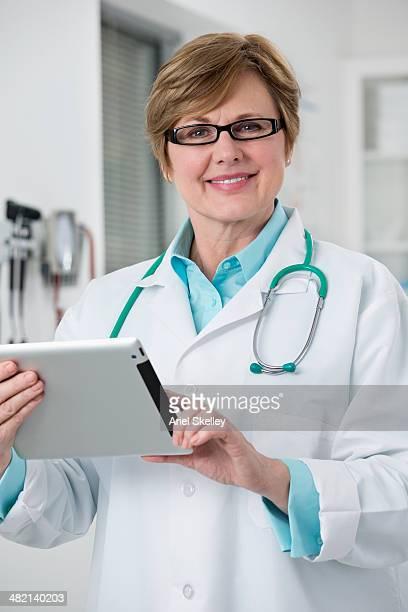 Caucasian doctor using digital tablet in office