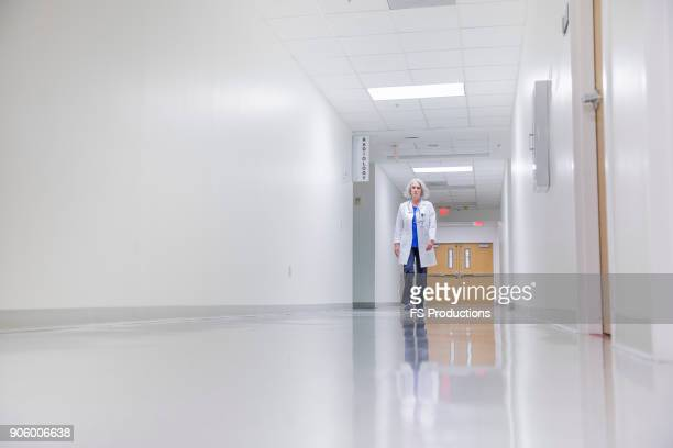 caucasian doctor walking in hospital - corridor stock pictures, royalty-free photos & images