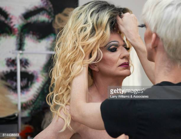 caucasian drag queen fixing colleague's wig in bathroom - young crossdressers stock photos and pictures