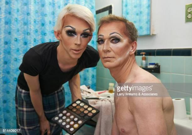 Caucasian drag queens displaying makeup in bathroom