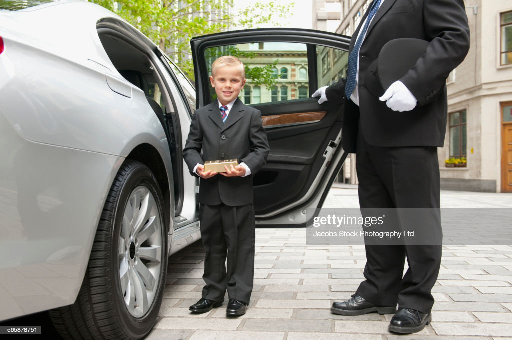 Caucasian driver opening car door for businessman boy : Stock Photo