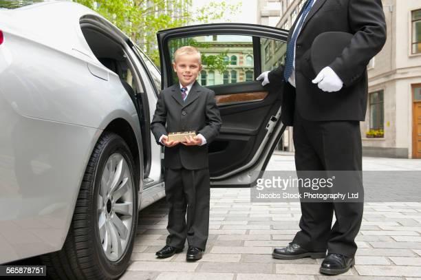 Caucasian driver opening car door for businessman boy