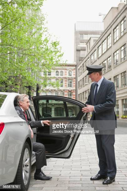 Caucasian driver opening car door for businessman