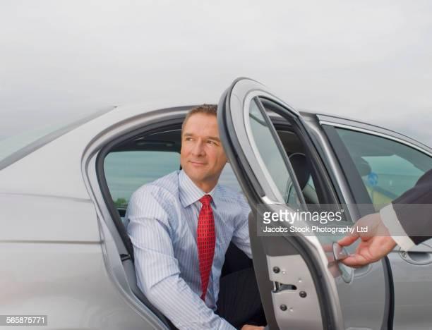 Caucasian driver opening door for businessman