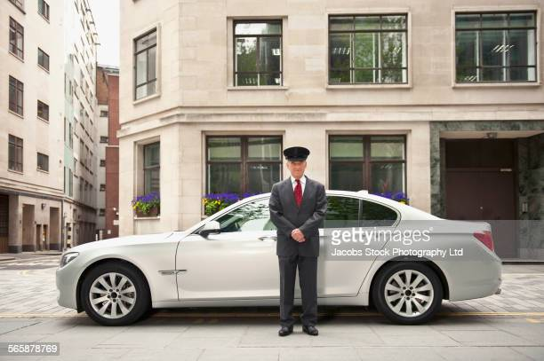 Caucasian driver standing near car in city