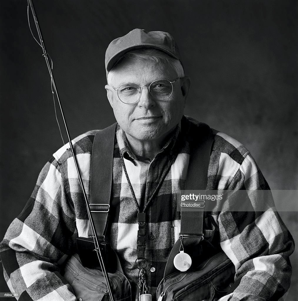A caucasian elderly man sits in his fly fishing gear : Stockfoto