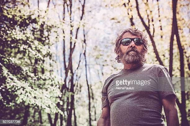 Caucasian elderly man with beard and sunglasses portrait in forest