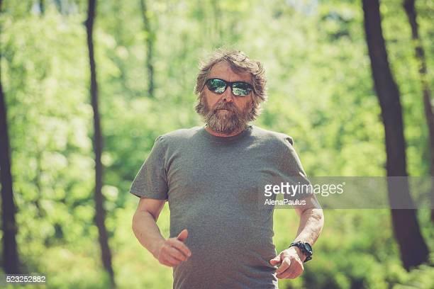 Kaukasier Älterer Mann mit Bart und Sonnenbrillen Laufen im Wald