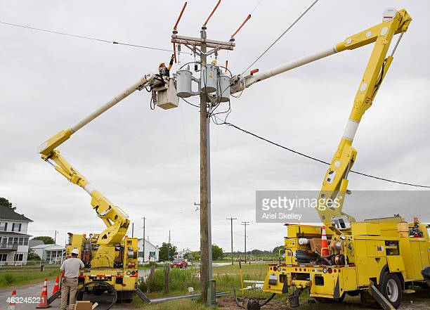 Caucasian electricians using cherry pickers at power line