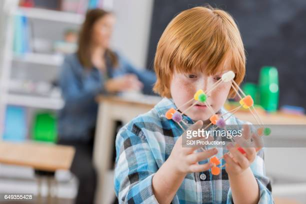 caucasian elementary school student concentrates on engineering project - gum drop stock photos and pictures
